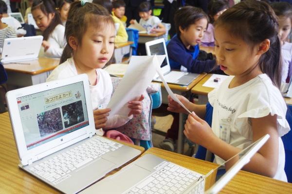 互いにタブレットを見せ合いながら交流する児童